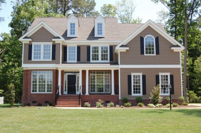 two-story home with lots of windows, brick on part of bottom and brown vinyl siding with white trim and black shutters